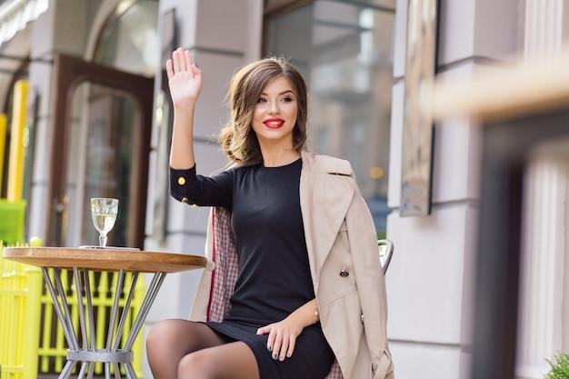 Heureuse Femme Adorable Agitant à Un Ami Alors Qu'il était Assis Dans La Cafétéria D'été Avec Un Verre De Vin Photo gratuit