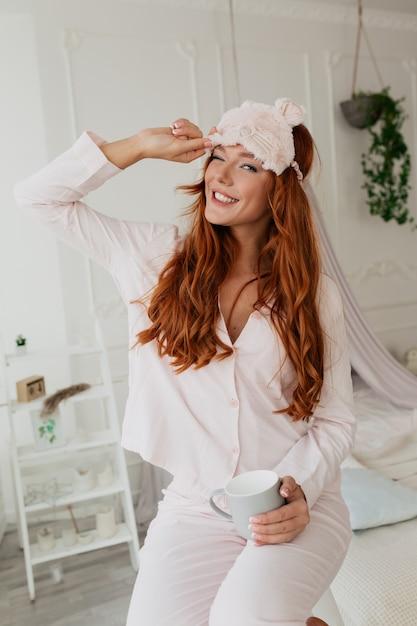 Heureuse Femme Adorable Avec De Longs Cheveux Ondulés Avec Un Masque De Sommeil Portant Un Pyjama Avec Du Café Le Matin à La Maison Photo gratuit