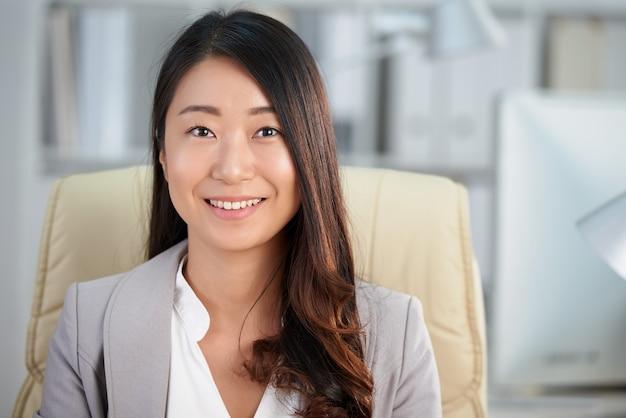 Heureuse femme d'affaires asiatiques assis dans le bureau et souriant Photo gratuit