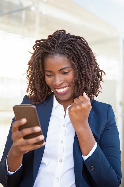 Heureuse femme d'affaires joyeuse tenant un téléphone portable Photo gratuit