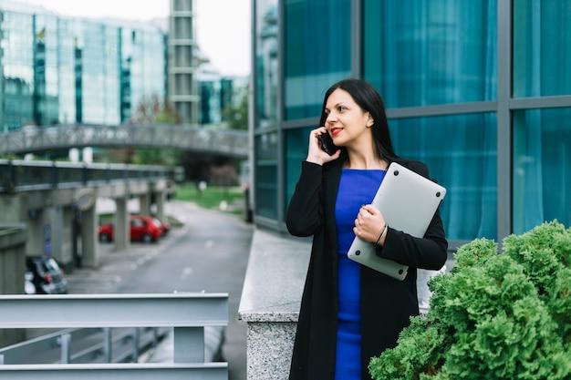 Heureuse femme d'affaires avec ordinateur portable parlant sur smartphone Photo gratuit