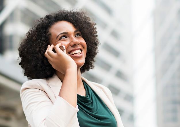 Heureuse femme d'affaires parlant au téléphone Photo gratuit
