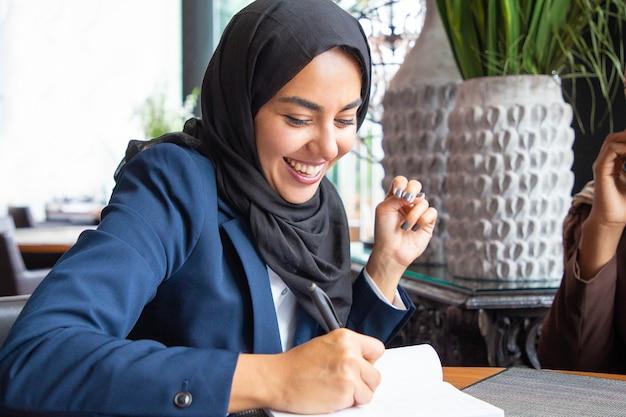 Heureuse Femme D'affaires Prenant Des Notes Photo gratuit