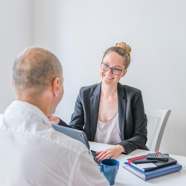 Heureuse femme d'affaires en regardant son partenaire au bureau Photo gratuit