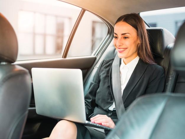 Heureuse femme d'affaires voyageant en voiture à l'aide d'un ordinateur portable Photo gratuit