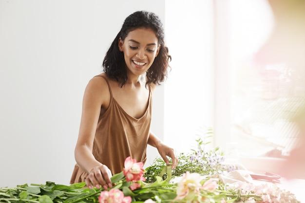 Heureuse Femme Africaine Tendre Souriant Faisant Un Bouquet De Fleurs Sur Le Lieu De Travail Sur Le Mur Blanc. Photo gratuit