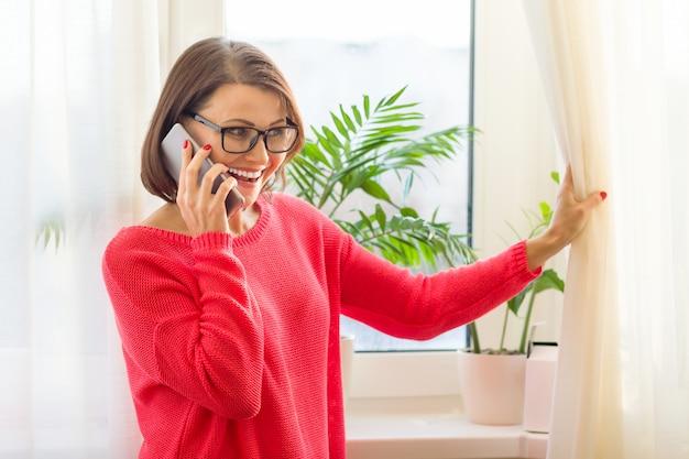 Heureuse femme d'âge moyen femme parlant sur un téléphone mobile Photo Premium