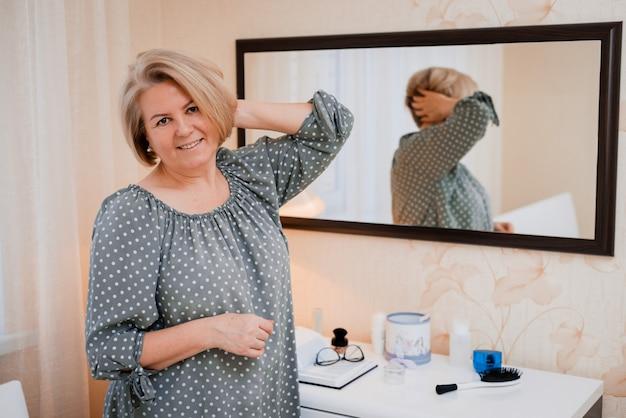 Heureuse Femme âgée D'âge Moyen Préens Et Ajuste Ses Cheveux Devant Le Miroir De La Coiffeuse Photo Premium