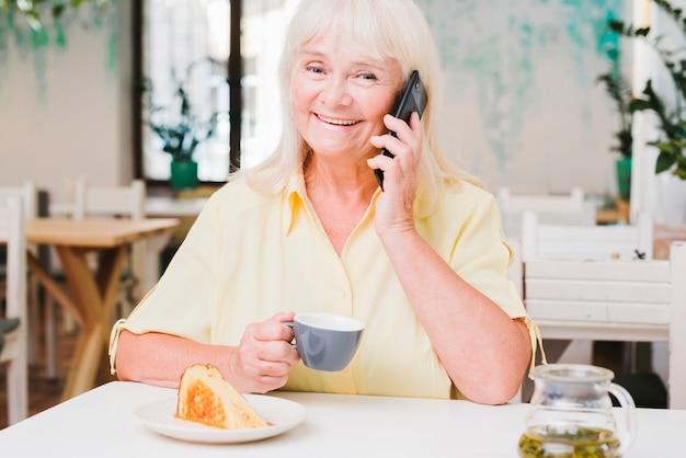 Heureuse femme âgée souriante parlant au téléphone Photo gratuit