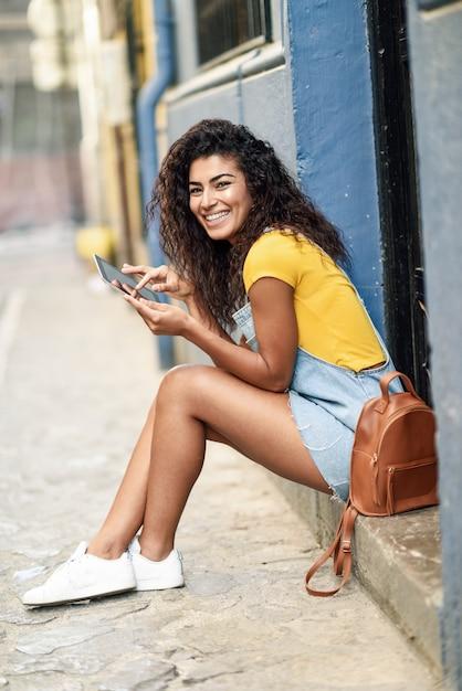 Heureuse femme arabe assise sur une marche urbaine avec une tablette numérique Photo Premium