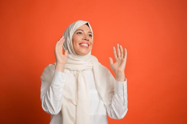Heureuse Femme Arabe Surprise En Hijab. Portrait De Jeune Fille Souriante, Posant Au Fond De Studio Rouge. Jeune Femme émotionnelle. émotions Humaines, Concept D'expression Faciale. Photo gratuit