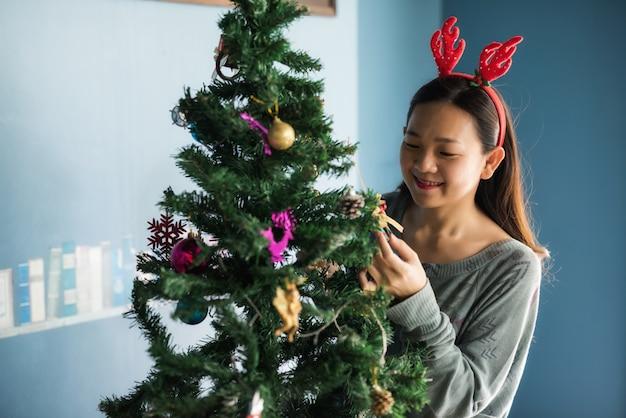 Heureuse femme asiatique à l'arbre de noël Photo Premium