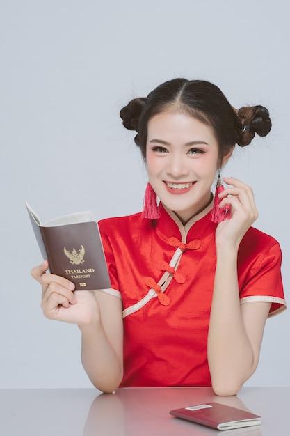 Heureuse femme asiatique en costume chinois traditionnel détenteur d'un passeport Photo Premium