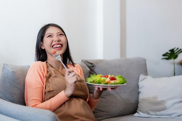 Heureuse Femme Asiatique Enceinte Assis Et Manger Des Aliments Sains De Salade De Légumes Naturels Et Assis Sur Le Canapé Photo Premium