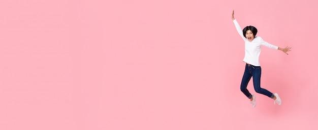 Heureuse femme asiatique énergique portant des vêtements décontractés, saut Photo Premium