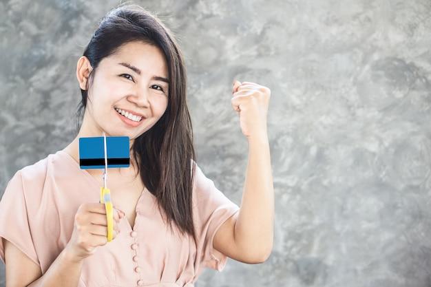 Heureuse femme asiatique libre de dette main coupe carte de crédit en ciseaux avec visage souriant Photo Premium