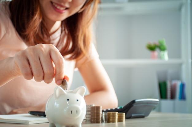 Heureuse Femme Asiatique Met De L'argent Dans Une Tirelire Photo Premium