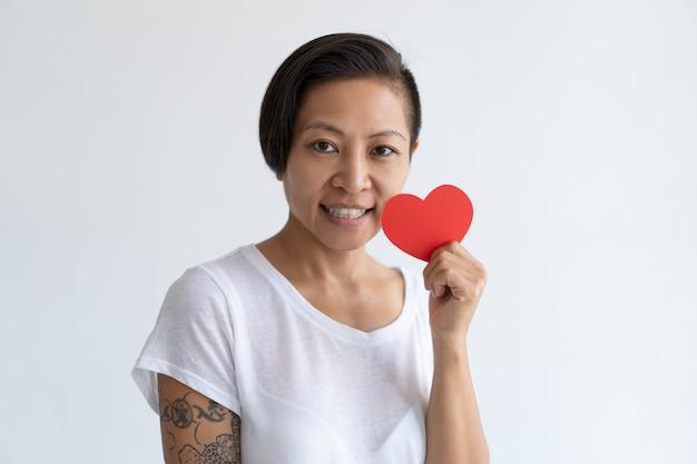 Heureuse femme asiatique posant avec coeur de papier Photo gratuit