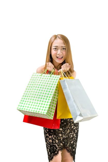 Heureuse femme asiatique en robe tenant des sacs à provisions Photo Premium