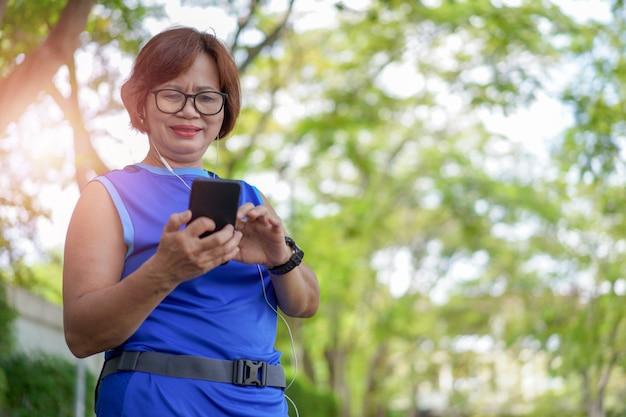 Heureuse femme asiatique senior tenant un téléphone intelligent avec de la musique Photo Premium