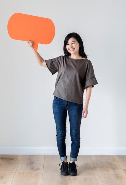 Heureuse femme asiatique tenant bulle de dialogue fond Photo gratuit
