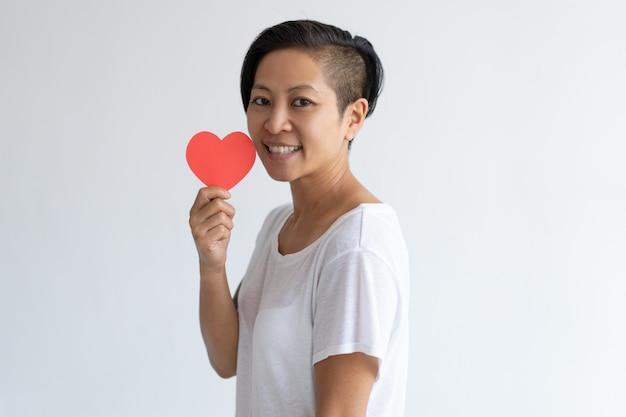 Heureuse femme asiatique tenant coeur de papier Photo gratuit