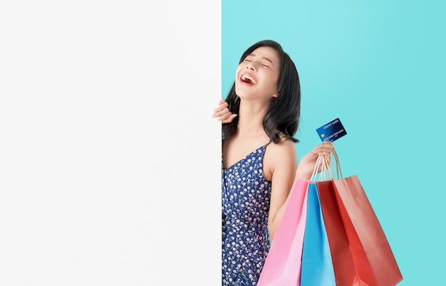 Heureuse femme asiatique tenant des sacs à provisions avec carte de crédit et montrant un panneau vierge. Photo Premium