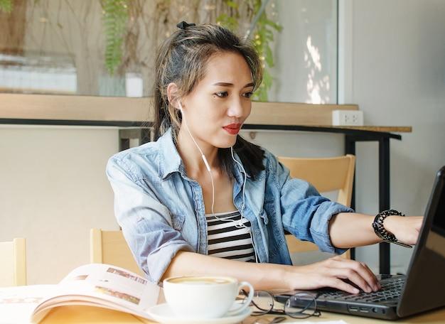 Heureuse femme asiatique travaillant dans un café. Photo Premium