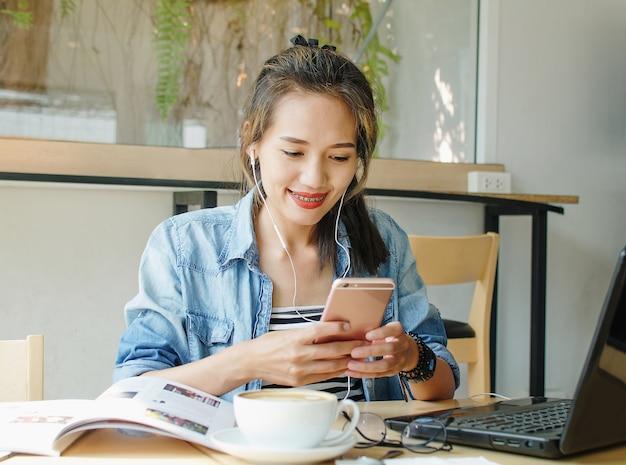 Heureuse femme asiatique travaillant et utiliser un téléphone intelligent dans un café Photo Premium