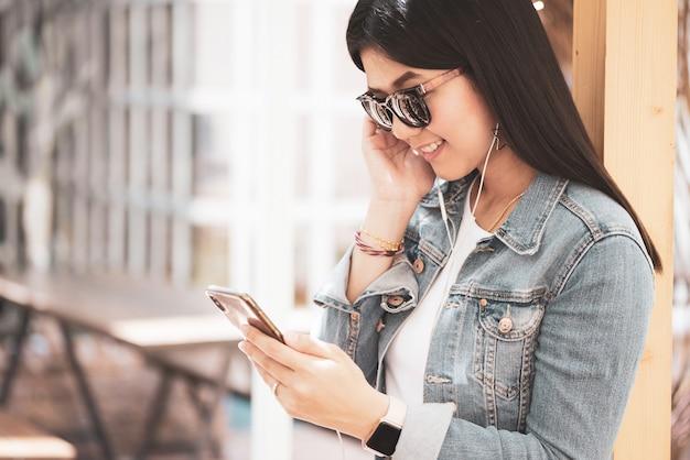 Heureuse femme asiatique utilisant un téléphone pour écouter de la musique. Photo Premium