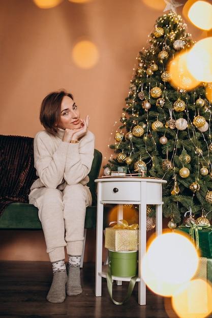 Heureuse femme assise sur un canapé près de l'arbre de noël Photo gratuit
