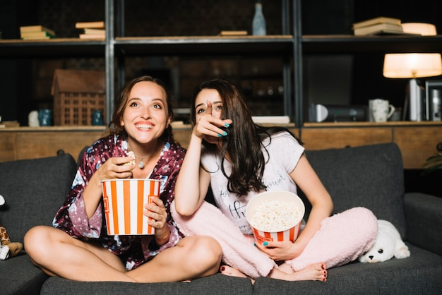 Heureuse femme assise à côté de son amie en pointant le doigt en regardant un film Photo gratuit