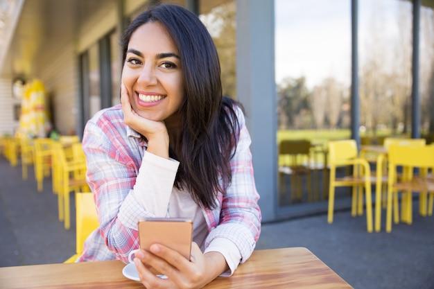 Heureuse femme assise dans le café de rue avec smartphone et café Photo gratuit