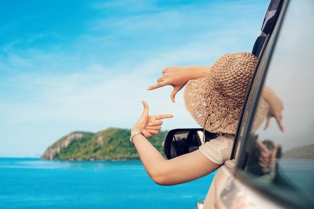 Heureuse femme assise dans la voiture et voyager saison estivale sur la mer au repos et journée spéciale pour les vacances. Photo Premium