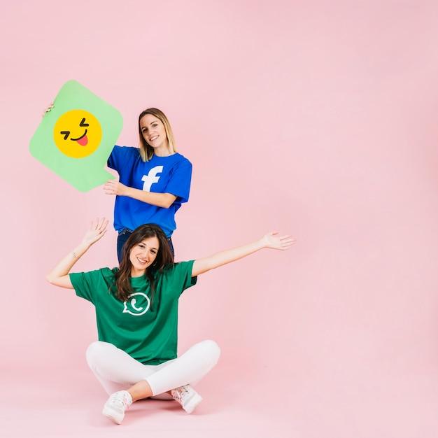 Heureuse femme assise devant son ami avec un clin de œil emoji bulle Photo gratuit
