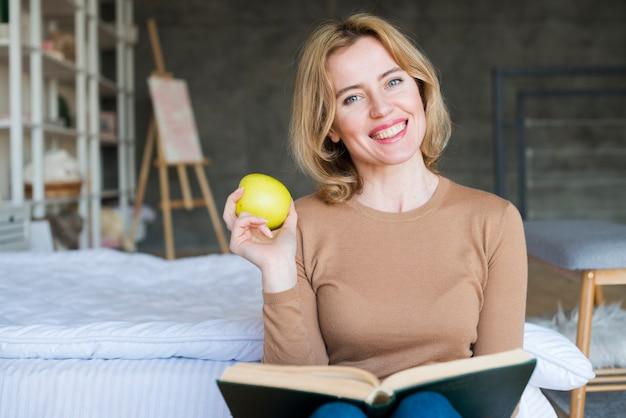 Heureuse femme assise avec livre et pomme Photo gratuit
