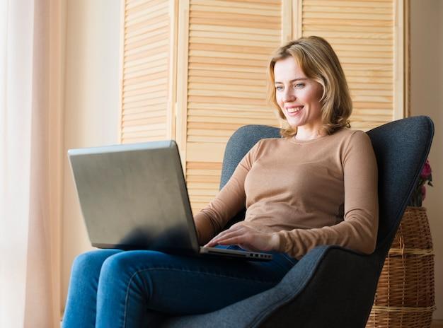 Heureuse femme assise et utilisant un ordinateur portable Photo gratuit