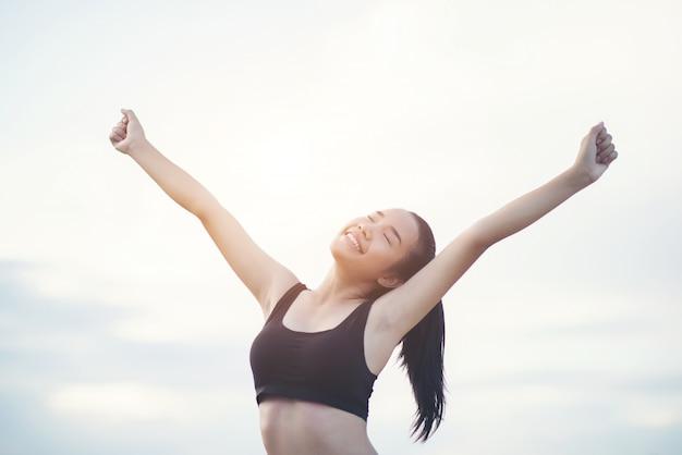 Heureuse femme athlétique souriante avec les bras tendus Photo gratuit