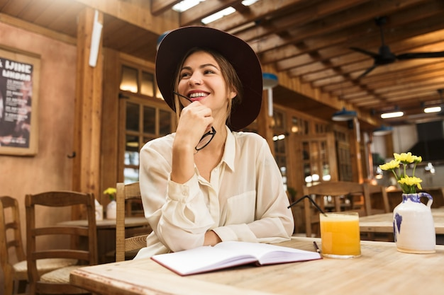 Heureuse Femme Au Chapeau Assis à La Table De Café à L'intérieur Photo Premium