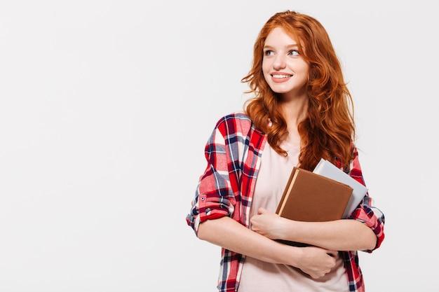 Heureuse Femme Au Gingembre En Chemise Tenant Des Livres Et En Détournant Les Yeux Photo gratuit