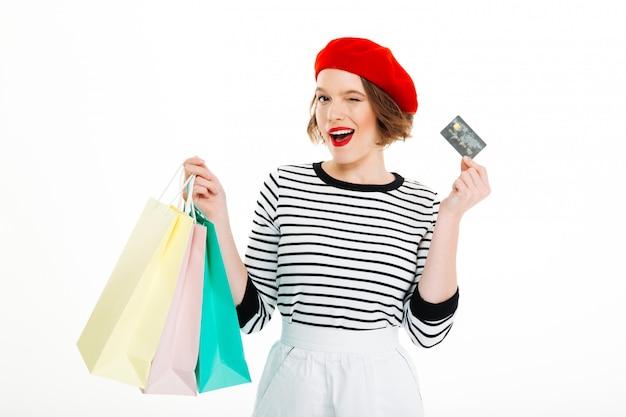Heureuse Femme Au Gingembre Avec Des Paquets Tenant Une Carte De Crédit Et Un Clin D'œil à La Caméra Sur Gris Photo gratuit