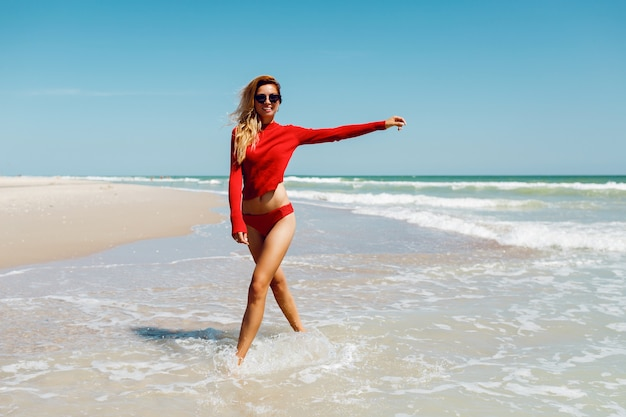 Heureuse Femme Blonde Au Bord De La Mer Souriant Heureux. Concept De Vacances D'été. Amzing Plage Tropicale. Porter Un Bikini Rouge. Corps Bronzé Parfait Et Silhouette élancée. Photo gratuit