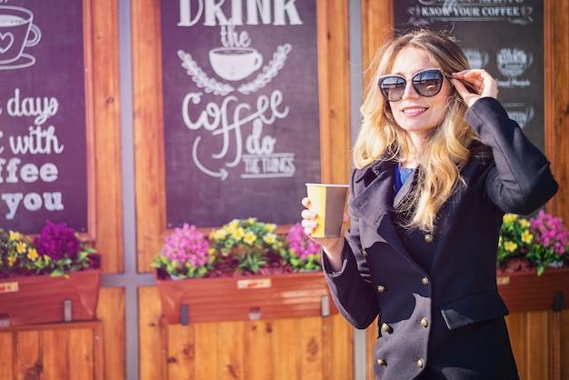 Heureuse femme blonde caucasienne, boire du café Photo Premium