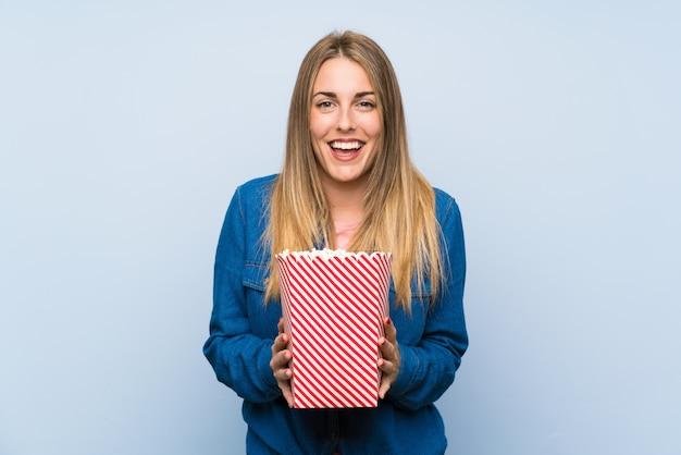 Heureuse femme blonde avec des pop-corn sur le mur bleu Photo Premium