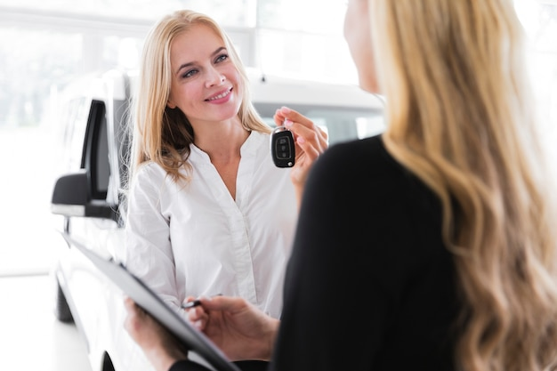 Heureuse femme blonde tenant des clefs de voiture Photo gratuit