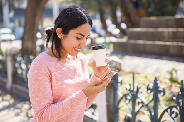 Heureuse femme buvant du café et en naviguant sur l'extérieur du smartphone Photo gratuit