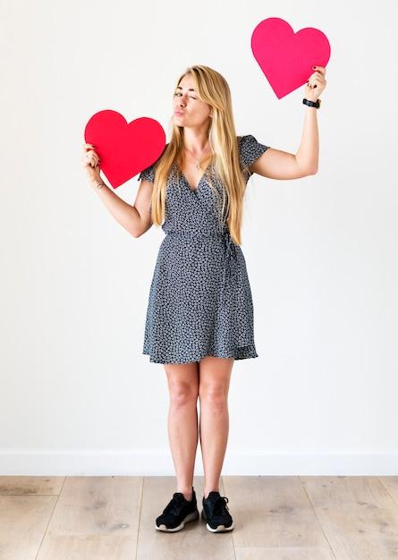 Heureuse femme caucasienne tenant des coeurs rouges Photo Premium