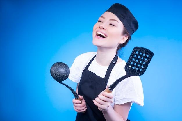 Heureuse Femme Chef Riant Et Tenant Des Ustensiles De Cuisine Dans Ses Mains Contre Le Mur Bleu Photo gratuit