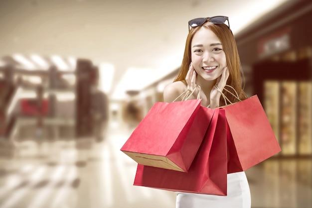 Heureuse femme chinoise avec des sacs en papier rouge sur le centre commercial Photo Premium