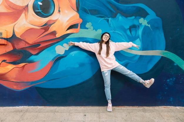 Heureuse femme dansant devant le mur de graffitis colorés Photo gratuit
